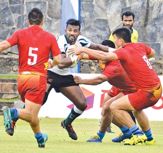 Sri Lanka's Gayan Weeraratne attempts to break through three Chinese defenders during their Asian Rugby Sevens match at the Racecourse ground in Colombo yesterday. Sri Lanka won the match 19-12    Pic: Saman Mendis