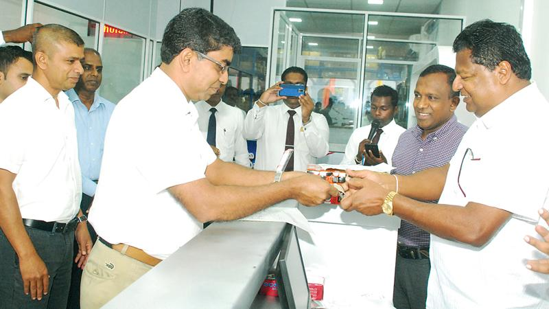 From left: Chairman Ideal Group Nalin Welgama, conducts the first transaction for the newly opened Ideal Motors Spare Parts Store in Panchikawatte with Jagath Jayasinghe of Lumina Motors Ltd. and Automotive Director, Ideal Motors, Chaminda Wanigarathne, cutting the ribbon to declare open the new Ideal Motors spare parts store in Panchikawatte.