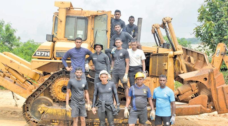 The Navy personnel with the salvaged bulldozer