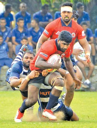 CR flanker Joel Perera attempts to break through a tackle by the Navy defence in their Dialog League match at Welisara yesterday (Picture by Saman Mendis)