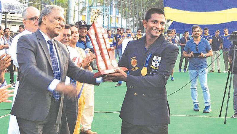 S. Thomas' College captain Dewmal Palapathwala receives the Orville Abeynaike Memorial Trophy from Dr. Kapila Waidyaratne