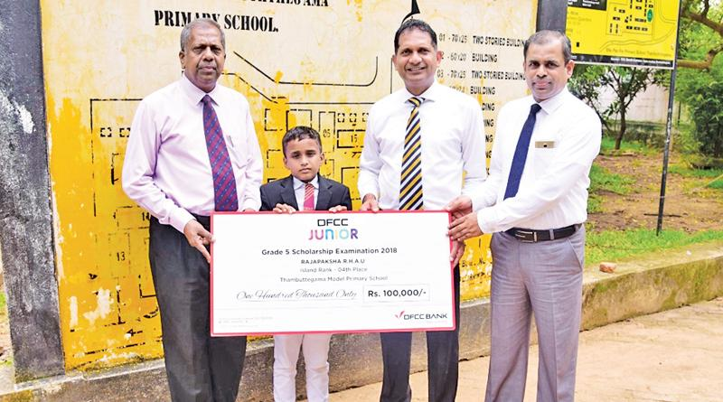 Ayodya Udan Rajapaksha of Model Primary School Thambuttegama, receives the cheque from DFCC's Regional Manager, Candiah Jegarajah, Vice President, Liabilities and Trade Business Development, Anton Arumugam and Product Champion Nuwan Medonza.