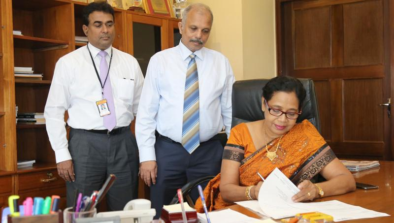 Chairperson of People's Bank, Mrs Sujatha Cooray assumes duties. CEO/GM N. Vasantha Kumar  and Senior Deputy General Manager/Secretary to the Board of Directors, Rohan Pathirage look on.