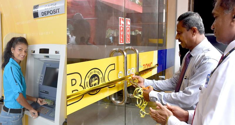 Deputy General Manager Sales and Channel Management C. Amarasinghe opens the 1000th ATM/CDM machine at the Kuliyapitiya second branch. Assistant General Manager North Western Province I.M.L Karunathilake looks on.