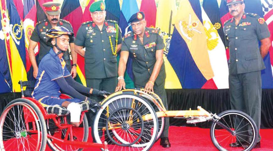 Commander of the Army, Lieutenant General Mahesh Senanayake   gifts Cpl. Karunarathna a wheel chair