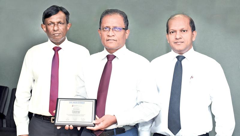 BOC CEO/ General Manager Senarath Bandara with the plaque awarded by the 'Asian Banker' for the top 500 Banks in the Asia-Pacific Region. BOC's CFO/ Deputy General Manager Corporate and Offshore Russell Fonseka (right) and Deputy General Manager Finance and Planning RMDV Jayabahu (left) look on.