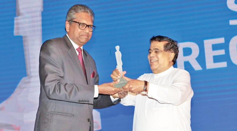 Dr. Harsha Cabral receives the award for 2018 from former Minister Nimal Siripala de Silva.