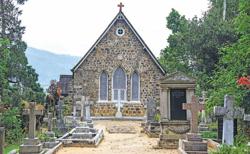 A front view of the stone built Warleigh Church amidst surrounding tombstones