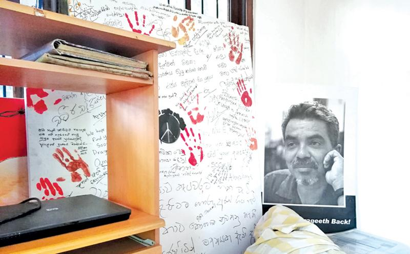 The white board signed by well-wishers and supporters on January 26, 2015, next to the large photograph  of a thoughtful Prageeth