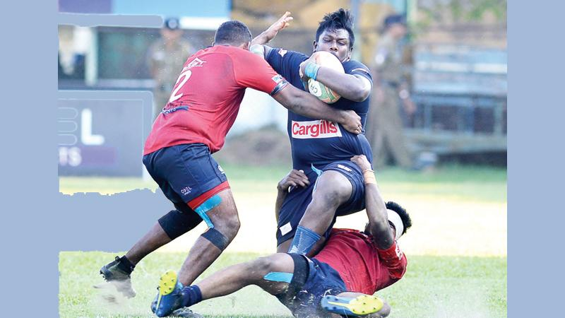 Police hooker Rasith Silva attempts to break through a tackle unleashed on him by two CR defenders in their Dialog League rugby match at Longden Place yesterday Picture by Thilak Perera