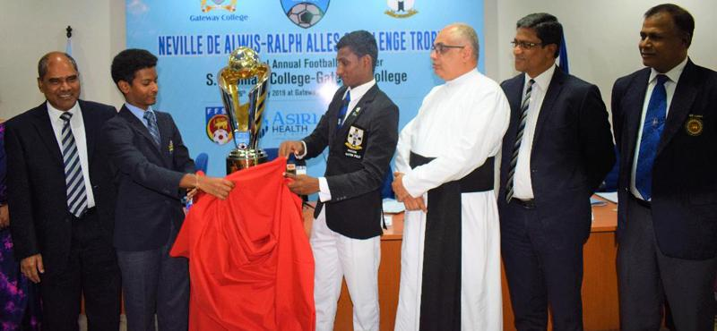 Gateway College captain Rashane Wijewardene (left) and S. Thomas' College captain DS Ebenezer unveil the Neville de Alwis-Ralph Alles Trophy they will play for in a soccer match as Dr. Harsha Alles (left)Chairman of Gateway and Rev. Marc Billimoria the Warden of S. Thomas' College look on    (PICTURE BY HERBERT PERERA )