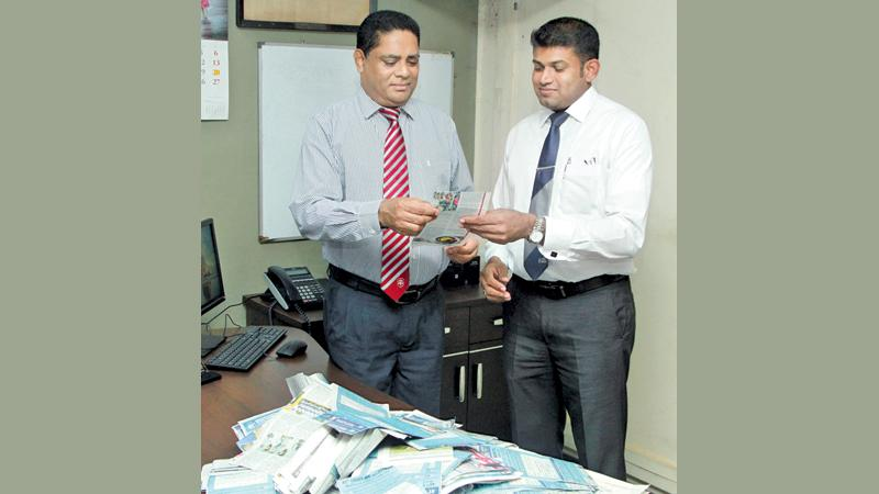 Deputy General Manager Finance, Virajith Shamendra Bois and Manager Advertising Suranga Dalugoda selecting the Readers Coupon No.8 winners of Observer - Mobitel School Cricketer 2018 at Lake House. Pic by Shan Rambukwella