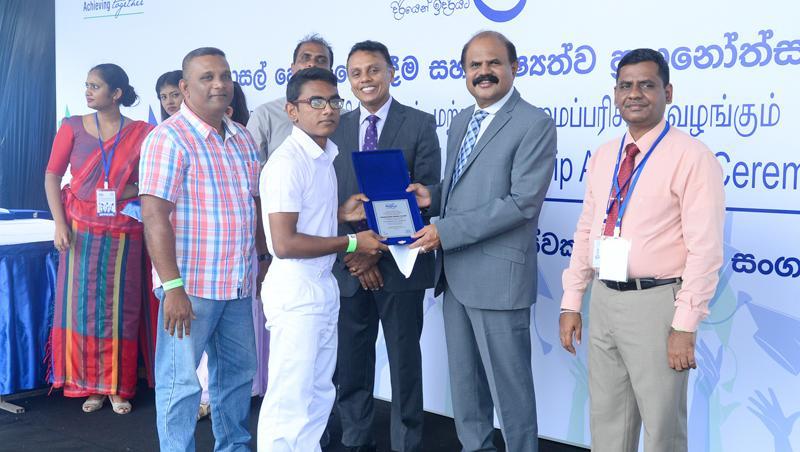 A student receives an award from Chairman Kumarasinghe Sirisena.