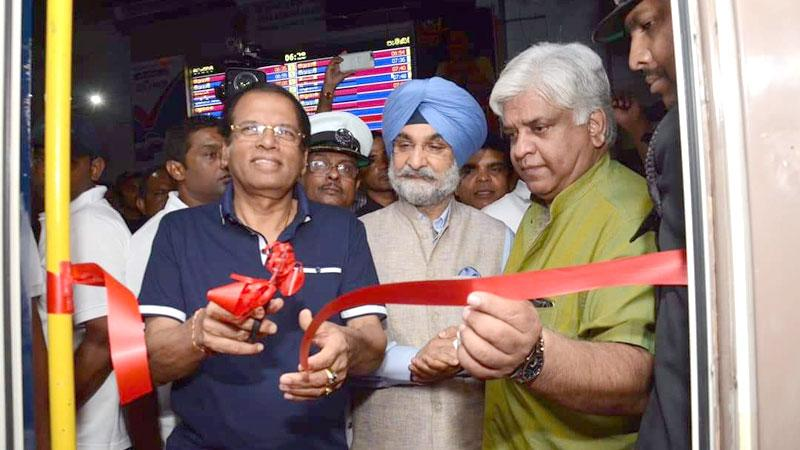 President Maithripala Sirisena cuts the ribbon to flag the train off while Minister Arjuna Ranatunge and Indian High Commissioner Taranjit Singh look on