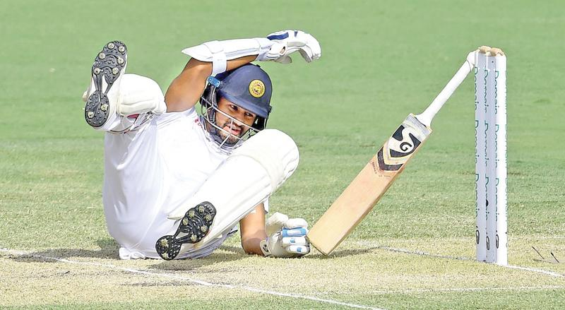 Dimuth Karunaratne falls to the ground after being hit by a ball from Australia's Pat Cummins on the second day of the second cricket Test at the Manuka Oval in Canberra yesterday (Photo by ISHARA S.  KODIKARA -AFP)