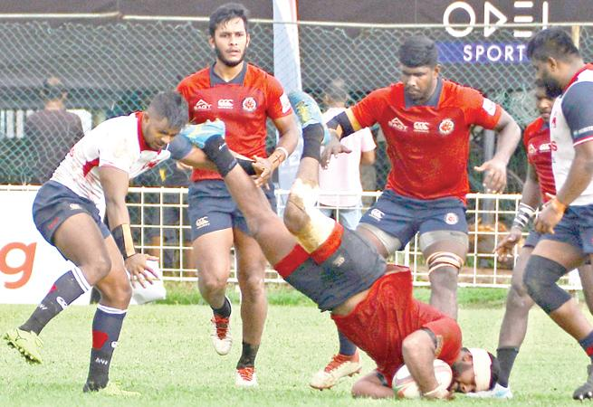 CR and FC player Omalka Gunaratne falls to the ground as his team-mates Joel Perera (right) and Rehan Silva (left) look on while Kandy's Richard Dharmapala moves in (Picture by Thilak Perera)