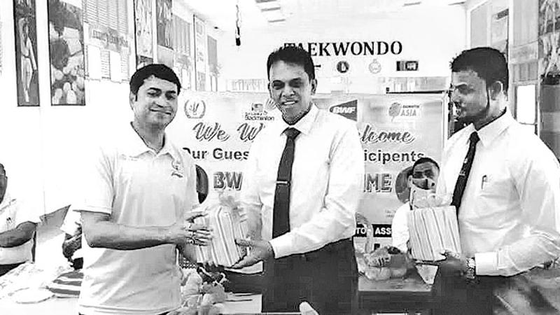 Sri Lanka Badminton Association chief Nishantha Jayasinghe handing over a memento to the Asian regional badminton officer Nikil Chandra at the Eastern Province in connection with the Shuttle Time program.