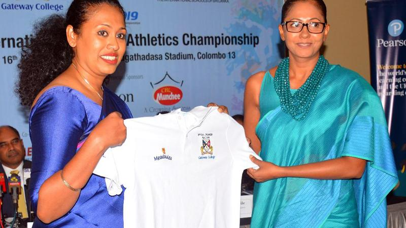 Nadeesha Chandrasekera (left), the head of marketing of Pyramid Wilmar handing over an official T-Shirt to Suranji Waduwala organising committee official of the International Schools Athletic Championship (Picture by Ranjith Asanka)