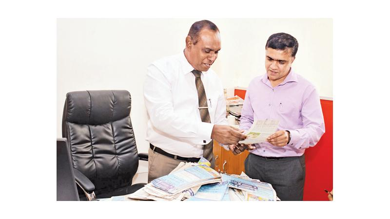 Senior Manager Advertising Sanath Preethijith (left) and Editor in Chief of Silumina Chaminda Wariyagoda selecting the Readers Coupon No.12 winners of the Observer - Mobitel School Cricketer 2019 contest at Lake House.  Pic by Saman Mendis