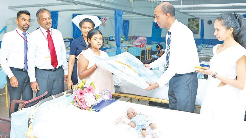 Chief Executive Officer and General Manager-Designate Rasitha Gunawardena presents a gift to a newborn baby at the De Soysa Hospital for Women in Borella.
