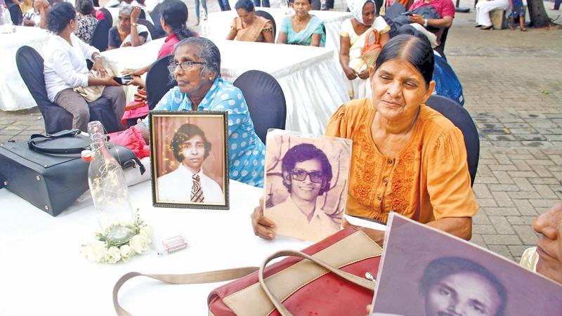 Dharamathi Palliyaguru (in yellow dress) and other  women  who wait endlessly