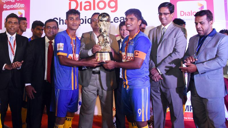 The victorious Defenders SC skipper Roshan Appuhamy (right) and the Most Valuable Player Asikoor Rahuman receiving the Dialog Champions Trophy from chief guest Manusha Nanayakkara