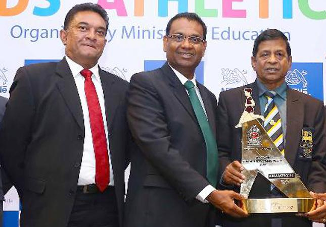 From left: Damitha Kulatunga Senior manager Corporate and Public Affairs of Nestle, Bandula Egodage Vice President Corporate Affairs of Nestle Lanka at the presentation of the trophy for Kids Athletics to Sunil Jayaweera Special Consultant Ministry of Education.