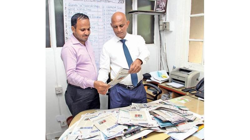 Manager Advertising Supplement Roy Jayasinghe (right) and Sports Editor Thinakaran, A.R. Fareeth selecting the Readers' Coupon No.16 winners of Observer - Mobitel School Cricketer 2019 at Lake House. Pic by Sulochana Gamage