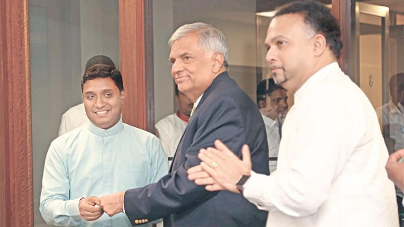 Prime Minister Ranil Wickremesinghe presents the UNP membership card to Talawakele-Lindula Urban Council Chairman Ashoka Sepala who obtained the UNP membership. UNP National Organiser and Plantation Industries Minister Navin Dissanayake looks on.