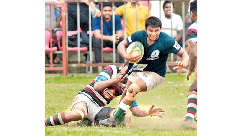 Isipathana College centre Manelka Ruberu is tackled by an opponent from Zahira College in their inter school rugby match at Havelock Park yesterday (Pic by Saman Mendis)