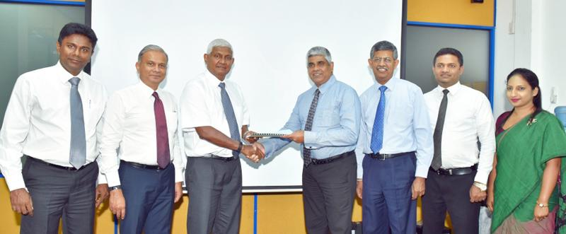 CHSL Chairman R. Renganathan (third from left and National Insurance Trust Fund (NITF) CEO Sanath de Silva exchange the agreement. Senior representatives of the two institutions look on.
