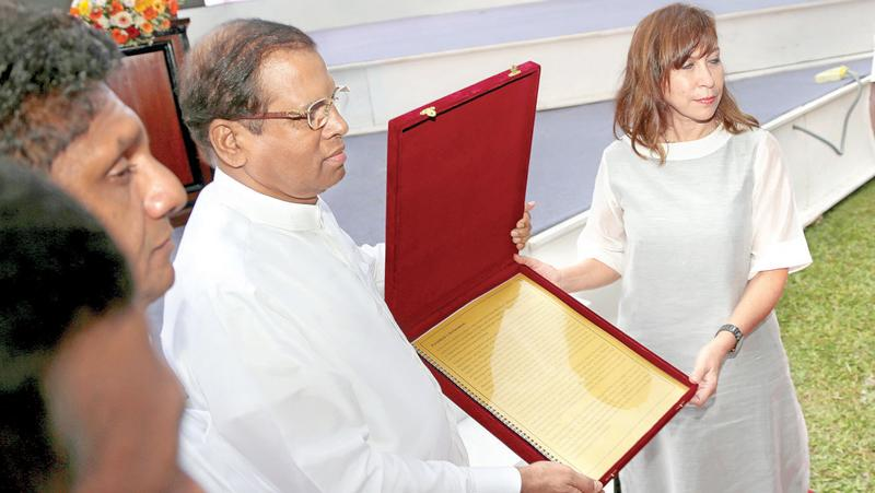 President Maithripala Sirisena handing over a request to UN Resident Coordinator Ms.Hanaa Singer seeking World Heritage recognition to the 'Tripitaka' - the sacred canon of Theravada Buddhism, written in  Pali, at the Dalada Maligawa premises yesterday.