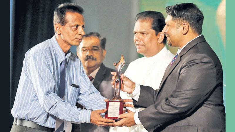 Sudam Gunasinghe receives his award from Non-Cabinet Minister of Media Ruwan Wijewardene