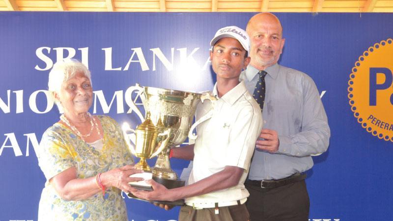 Boys winner S. Duwarshan receiving the Rukmini Kodagoda trophy from Shanthini Perera while Air Commodore Harsha Abeywickrema looks on