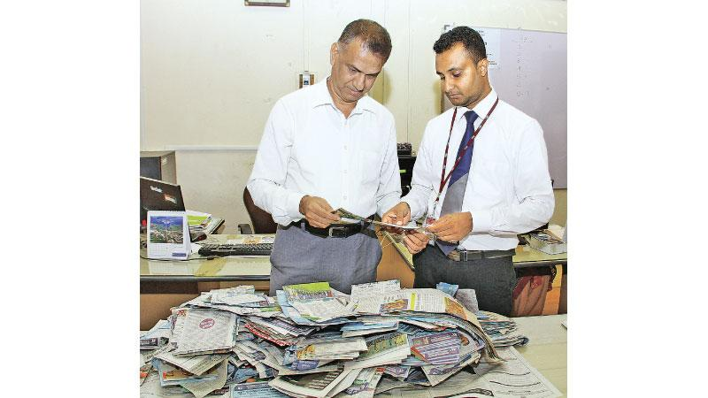 P.G.K. Madusanka, Manager Credit Control (right) and B.K.A. Senaka, Deputy Production Manager doing the draw of the winners at Lake House office.