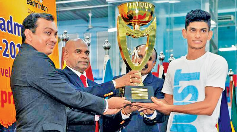 Buwaneka Gunatilleke receiving the men's Open champions trophy from the Army Commander Lt General Mahesh Senanayake at the Defenders Open Badminton at the Army Indoor Stadium Panagoda.