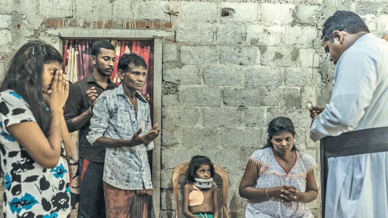 A priest prays with the family of a seven-year-old victim of a bomb blast