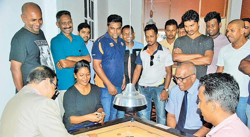 Carrom Federation president Prakrama Basnayake, Paralympic Committee president Major General Rajitha Ampemohotty and two national players Chalani Liyanage and Nishantha Fernando playing the exhibition game to mark the opening of the Premier Carrom Academy in Ganemulla