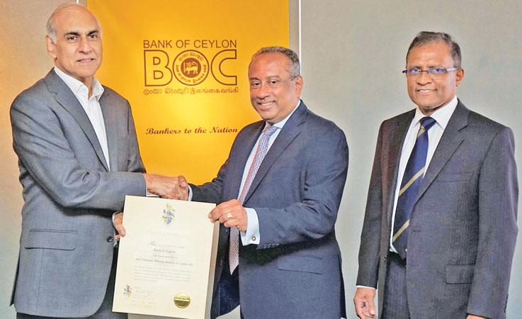 Brand Finance Lanka, Managing Director Ruchi Gunawardene presents the 'Most valuable Banking Brand' certificate to BOC Chairman, Ronald C. Perera at the Bank's boardroom recently. The Bank's CEO/ General Manager Senarath Bandara looks on.