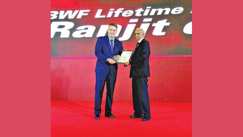 Professor Ranjit Silva (right) receiving his award from the president of the BWF Paul Eric Larsen