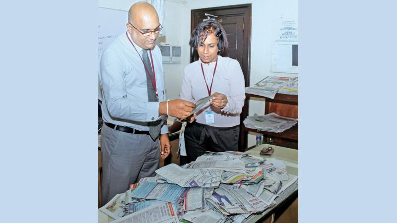 Manager Sales Field Operations, Shantha Pushpakumara (left) and Chief Librarian Rasika Nelanthi Liyanagama, selecting the Readers Coupon draw winners of Coupon No. 26 at Lake House. Pic: Saliya Rupesinghe