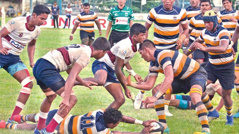 St. Peter's College winger Shenol Silva secures the ball against the forwards of Science College in their inter-school League rugby match at Bambalapitiya yesterday. (Picture by Thilak Perera)