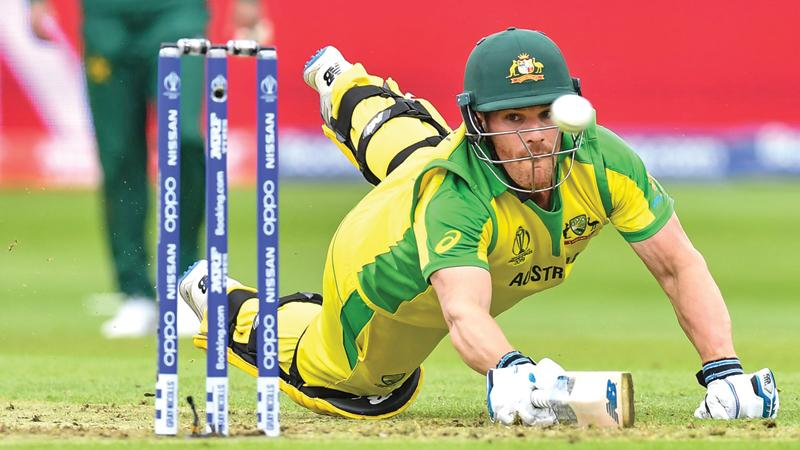 Australia's captain Aaron Finch dives to make his ground as the ball passes the stumps  AFP)