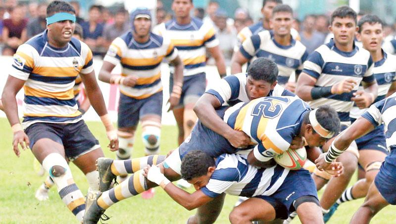Players from St. Peter's College and St. Joseph's College grapple for the ball in their rugby match at Bambalapitiya yesterday.  (Pic by Thilak Perera)