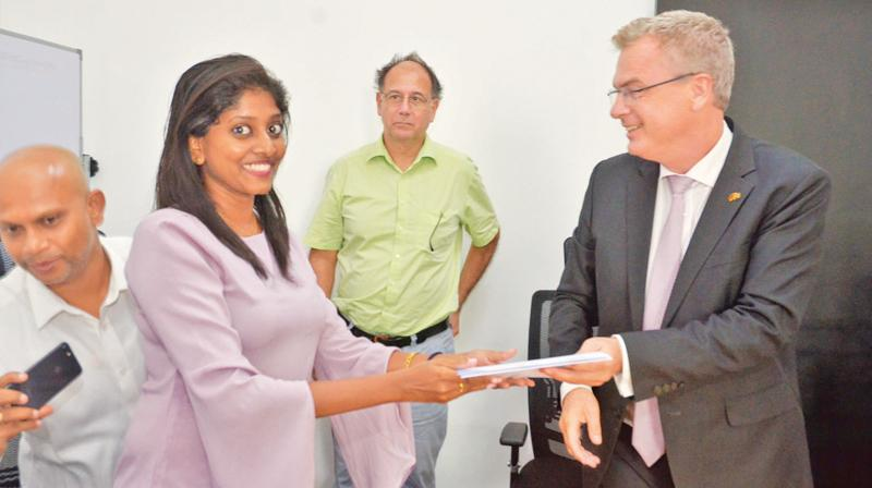 A young woman who completed the train-the-trainer course receives her certificate.