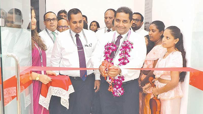 Director/CEO of Seylan Bank, Kapila Ariyaratne opens the branch. Bank officials look on.