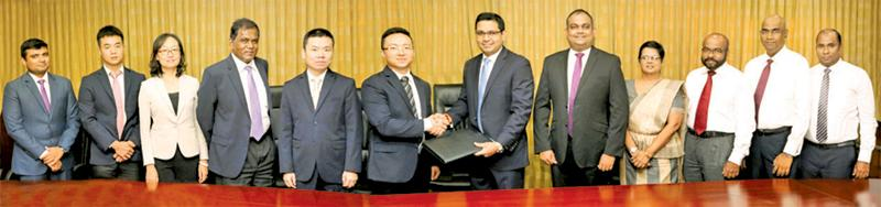 Commercial Bank Chief Operating Officer Sanath Manatunge (sixth from right) and Head of General Administration and Banking Department of Bank of China Limited – Colombo Branch,  Xin Tang, exchange the MoU. Representatives of the corporate and senior management of the two banks look on.