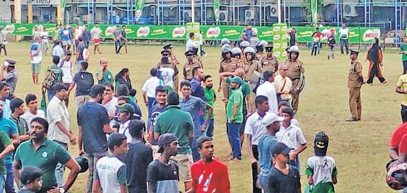 Anti-riot policemen move onto the ground at the Royal Sports Complex to control violence at last week's match between Isipathana and St. Peter's