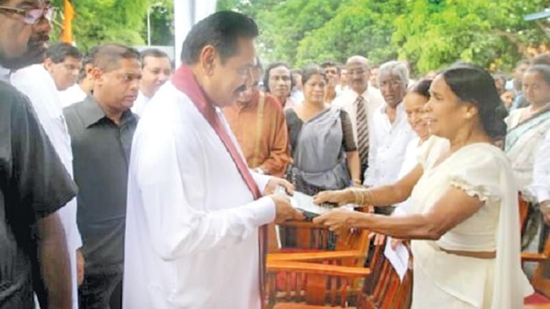 """Nirmala presents her book Premakeerthi to a startled President Rajapaksa saying""""The killer of my husband is under your protection."""""""