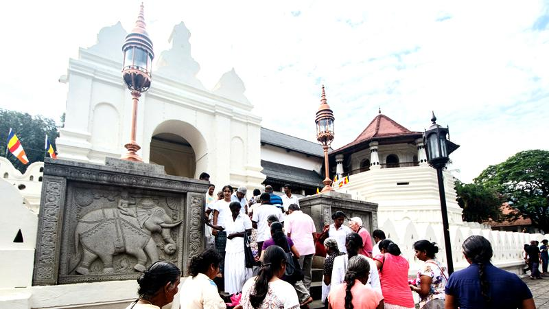THE MAJESTIC GUARDIANS: Pilgrims enter the Sri Dalada Maligawa near the stone walls of the temple which bear bas-relief testament to the  elephants' centuries of service